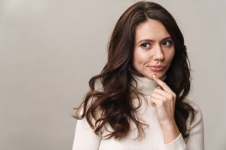 Photo of caucasian beautiful woman with long brown hair looking aside at empty space isolated over beige background