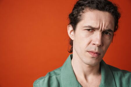 Image of displeased caucasian man posing and looking at camera isolated over orange background
