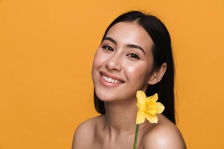 Beauty portrait of caucasian young brunette half-naked woman smiling and holding flower isolated over yellow background