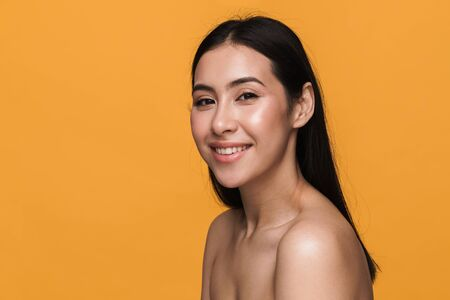 Beauty portrait of caucasian young brunette half-naked woman smiling with happy look isolated over yellow background