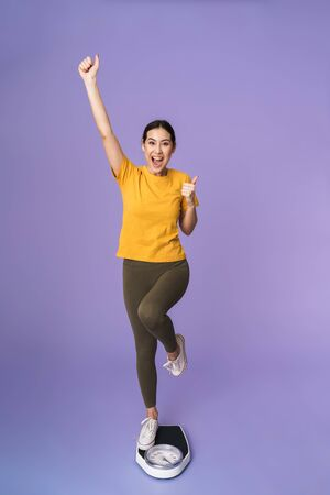 Full length of a cheerful young pretty sportswoman standing on scales isolated over violet background, celebrating
