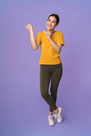Full length of a cheerful young pretty sportswoman standing isolated over violet background, presenting copy space
