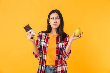 Image of confused caucasian woman holding apple and chocolate isolated over yellow background