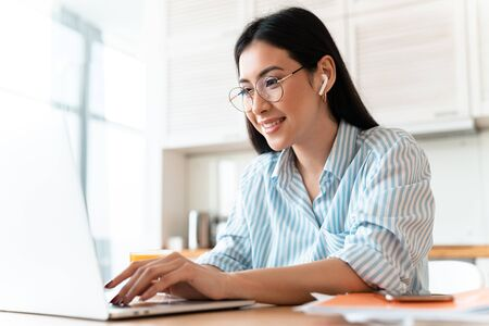 Image of a beautiful happy brunette young woman at the kitchen indoors at home using laptop computer and wireless earphones. Stockfoto