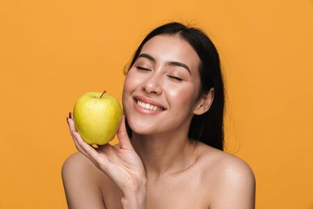 Beauty portrait of caucasian young brunette half-naked woman smiling and holding green apple isolated over yellow background