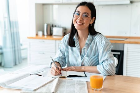 Image of a happy positive brunette young woman at the kitchen indoors at home writing notes studying. Archivio Fotografico