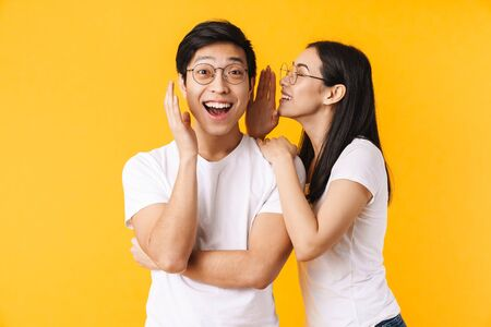 Image of smiling woman in eyeglasses whispering secret to surprised asian man isolated over yellow background