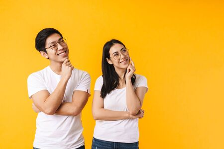 Portrait of a beautiful cheerful pensive young asian couple wearing casual clothing standing isolated over yellow background, looking away