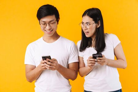 Portrait of a beautiful cheerful young asian couple wearing casual clothing standing isolated over yellow background, using mobile phones, woman is upset
