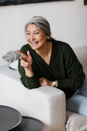 Photo of gray-haired joyful woman pointing finger aside and laughing while sitting on couch in living room