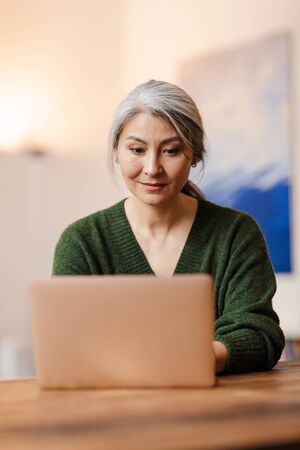 Image of amazing pleased mature beautiful grey-haired woman using laptop computer indoors.