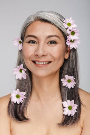 Image of a mature cheerful happy smiling grey-haired beautiful woman posing isolated over gray wall background with flowers in hair.