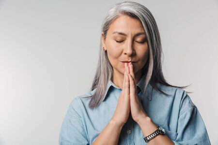Portrait of an elegant beautiful mature lady with long gray hair wearing casual clothes standing isolated over background, putting hands togethe in pray