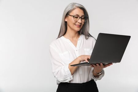 Image of adult mature woman wearing eyeglasses and office clothes using laptop computer isolated over white background Foto de archivo