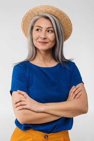 Image of adult mature woman with long gray hair wearing straw summer hat posing at camera isolated over white background Banque d'images