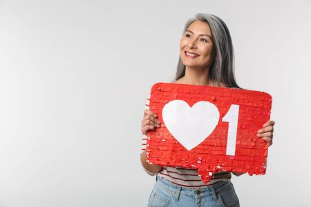 Image of adult mature happy woman with long white hair holding heart like symbol on placard isolated over gray background