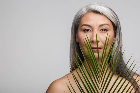 Beauty portrait of an attractive sensual mature topless woman with long gray hair standing isolated over gray background, posing with tropical leaf