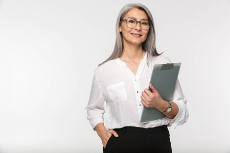 Portrait of an attractive smiling mature businesswoman in formal wear standing isolated over white background, holding a clipboard Foto de archivo