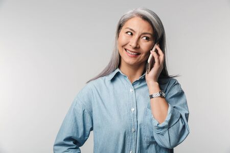 Image of adult mature woman with long white hair wearing shirt talking on cellphone isolated over gray background Banque d'images