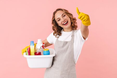 Image of a happy positive young housewife woman in gloves holding cleanser bottles isolated over pink wall background showing thumbs up.