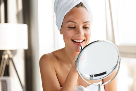 Photo of young joyful woman wrapped in white towels doing makeup while looking in mirror after shower Standard-Bild