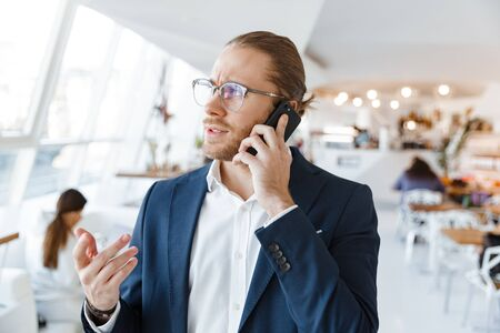 Image of handsome serious concentrated young businessman indoors in office talking by mobile phone.