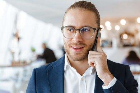Image of pleased young businessman indoors in office talking by mobile phone.