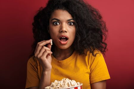 Image of shocked brunette african american woman with curly hair expressing wonder while holding popcorn bucket isolated over red background Stock Photo