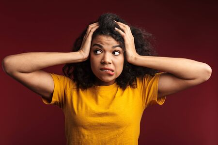 Image of nervous brunette african american woman with curly hair grabbing her head in panic isolated over red background