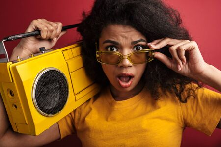 Image of surprised brunette african american woman with curly hair holding vintage boombox isolated over red background