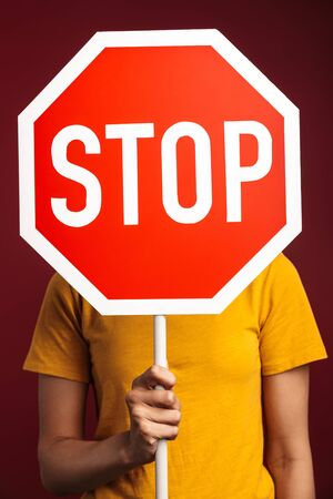 Image of outraged young brunette african american woman holding stop sign isolated over red background