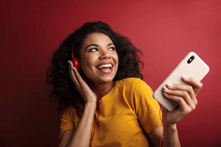 Image of beautiful brunette african american woman in headphones singing and holding cellphone isolated over red background Фото со стока