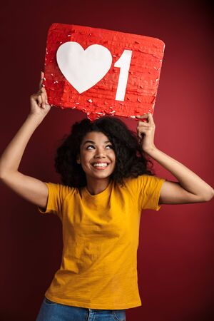 Image of beautiful brunette african american woman with curly hair laughing and holding like symbol placard isolated over red background