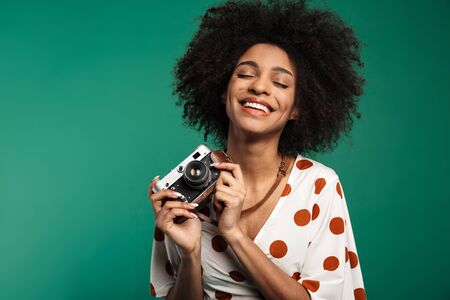 Portrait of a happy young african woman standing isolated over green background, wearing summer clothes, holding photo camera