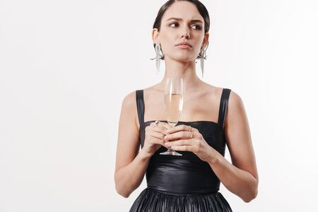 Image of charming young glamorous woman frowning and holding glass of champagne isolated over white background
