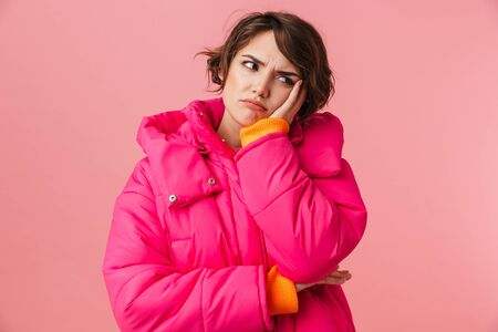 Portrait of young displeased woman in warm coat propping her head and looking aside isolated over pink background