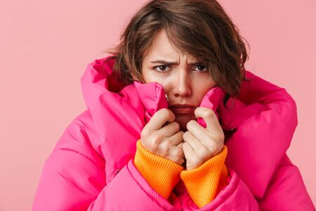 Portrait of displeased young woman in warm coat is freezing and looking at camera isolated over pink background