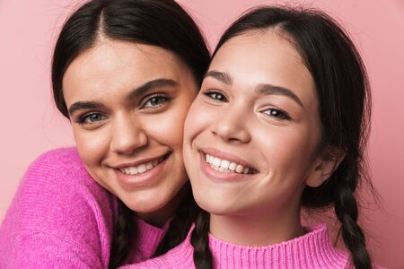 Two cheerful cute teenage girls having fun isolated over pink background, grimacing, hugging