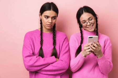 Image of upset offended teenage girl standing by her happy female friend with cellphone isolated over pink background