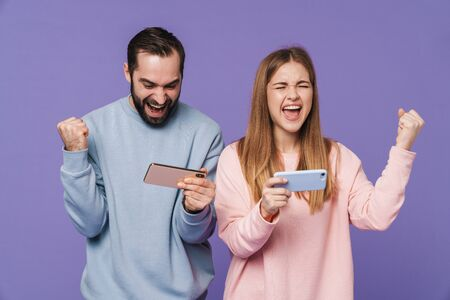 Image of excited emotional loving couple isolated over purple background play games by mobile phones make winner gesture.