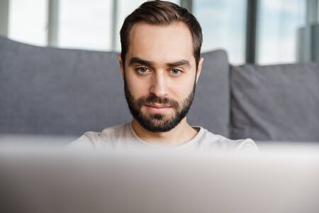 Image of a concentrated young man indoors at home using laptop computer.