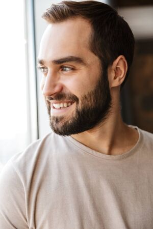 Handsome smiling young bearded man standing at the window at home, looking away