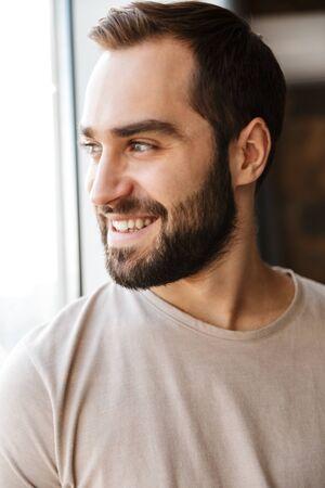 Hübscher lächelnder junger bärtiger Mann, der zu Hause am Fenster steht und wegschaut