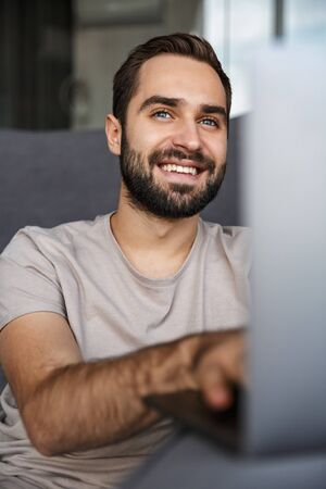 Image of a smiling positive young man indoors at home on sofa using laptop computer. 写真素材