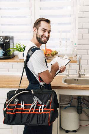 Image of young caucasian plumber man in uniform holding bag with equipment and clipboard while working in apartment