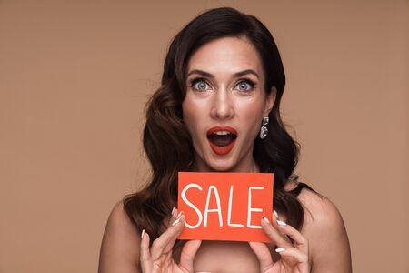 Beauty portrait of brunette gorgeous adult half-naked woman holding sale card isolated over beige background Stock fotó