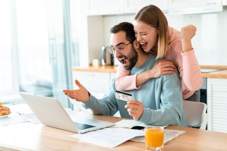 Portrait of young excited couple hugging while working with laptop and holding credit card in cozy kitchen at home