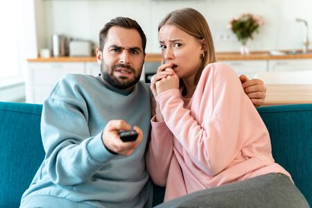 Portrait of young scared couple hugging and watching TV while sitting on sofa in cozy room at home