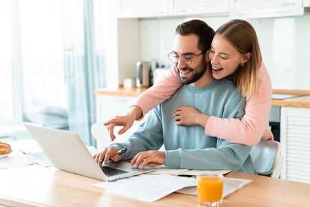 Portrait of young smiling couple hugging while working with laptop and documents in cozy kitchen at home Imagens