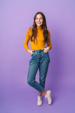 Full length image of young beautiful woman with long brown hair smiling and posing at camera isolated over violet background